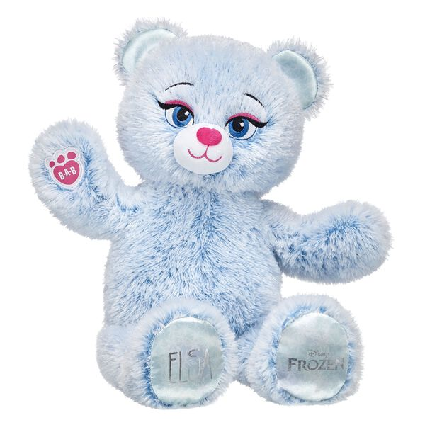 Elsa Inspired Bear is back and updated with a new look! This furry friend has soft fur that's a swirly mix of icy blue and snow white colours. She also has her name on one paw pad and the official Disney Frozen logo on the other. Add Elsa's signature dress to your Disney Frozen collection and relive the magic! © Disney