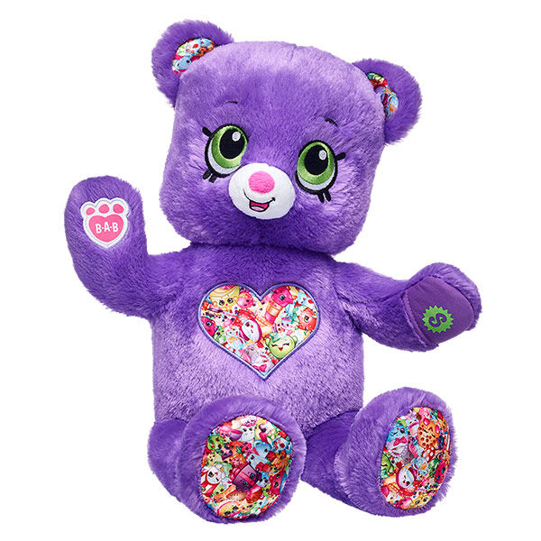 Experience love, fun and laughter with Shopkins Bear! With soft purple fur and bright green eyes, this adorable furry friend also features a cute heart with some of your favorite Shopkins characters on its stomach. Plus, Shopkins Bear comes with an exclusive collectible Shopkins figure that's the perfect size for the special pocket on its left paw! With more Shopkins outfits and accessories to choose from, Shopkins Bear is always in style! © 2013 Moose. Shopkins™ logos, names and characters are licensed trademarks of Moose Enterprise (INT) Pty Ltd. All rights reserved.
