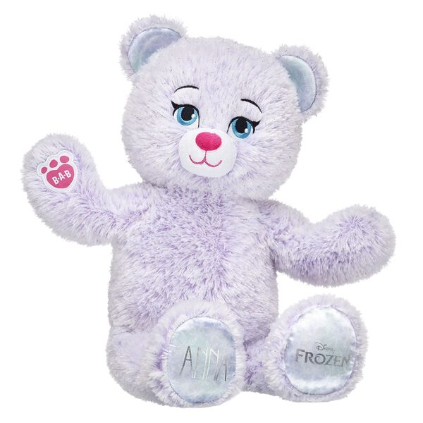 Anna Inspired Bear is back and updated with a new look! This furry friend has soft fur that's a swirly mix of violet and snow white colours. She also has her name on one paw pad and the official Disney Frozen logo on the other. Add Anna's signature dress to your Frozen collection and relive the magic! © Disney