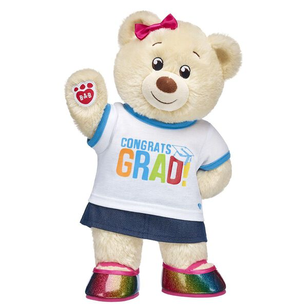 """Graduation is just the start of a brand new adventure! As the Class of 2018 looks toward the future, you can send them off with a furry friend by their side. Lil' Pudding Cub is cute as can be in this colourful gift set! <p>Price includes:</p>  <ul>    <li>Lil' Pudding Cub </li>     <li>Congrats Grad T-Shirt</li>    <li>Sparkly Denim Skirt</li>    <li>Rainbow Sparkle Flats</li>    <li>Rainbow Bows 6 pc.</li> </ul>"""