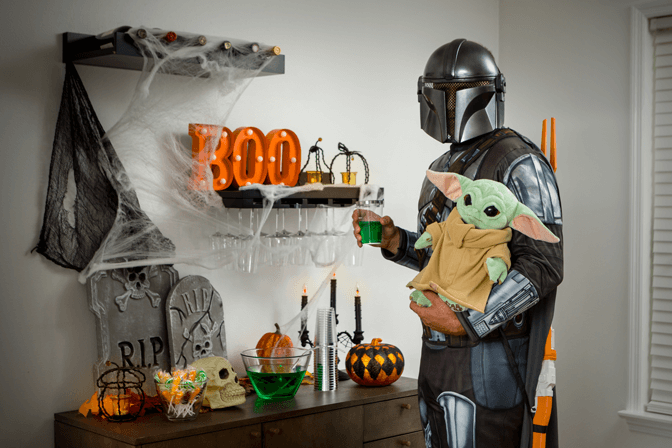 adult in the mandalorian costume with the child