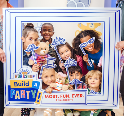 Kids posing for photo in cardboard picture frame