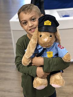 Child Hugging Stuffed Bunny in Police Uniform